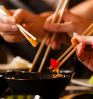 Photo of people using chopsticks to eat asian food