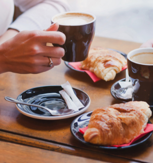 Photo of a person drinking coffee at a table with croissants on plates.