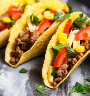 Photo of tacos with meat, cilantro, tomatoes and corn